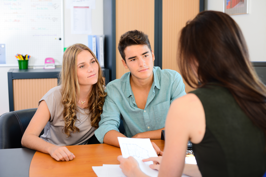 happy young couple getting advice in office from a beautiful business woman